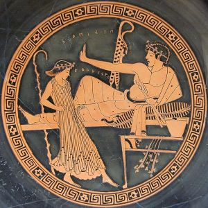Symposium scene: a reclining youth holds an aulos in one hand and gives another one to a female dancer. Tondo from an Attic red-figured kylix, ca. 490-480 BC. From Vulci. Image from Wiki Commons.